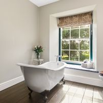 Bathroom with roll top bath and garden view